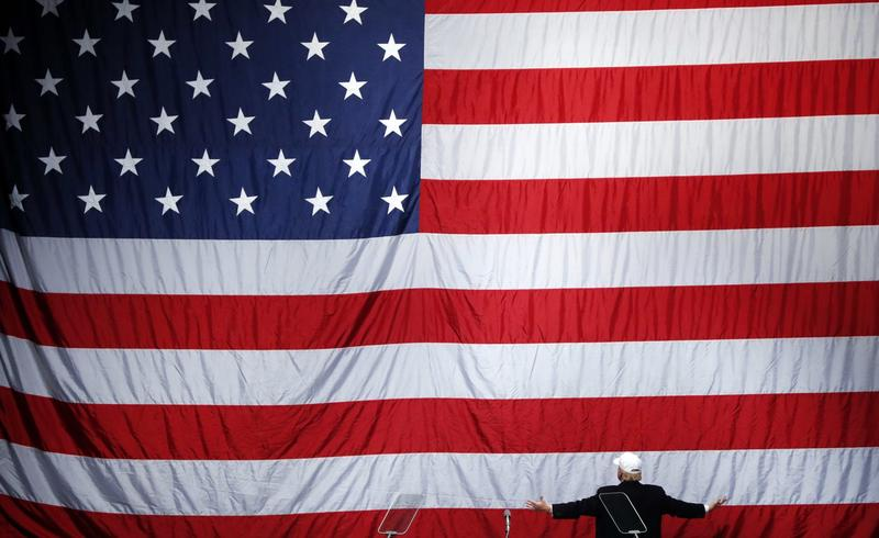 Republican presidential candidate Donald Trump turns to the American flag at a campaign rally in Sterling Heights, Mich., Sunday, Nov. 6, 2016. (Paul Sancya/AP)