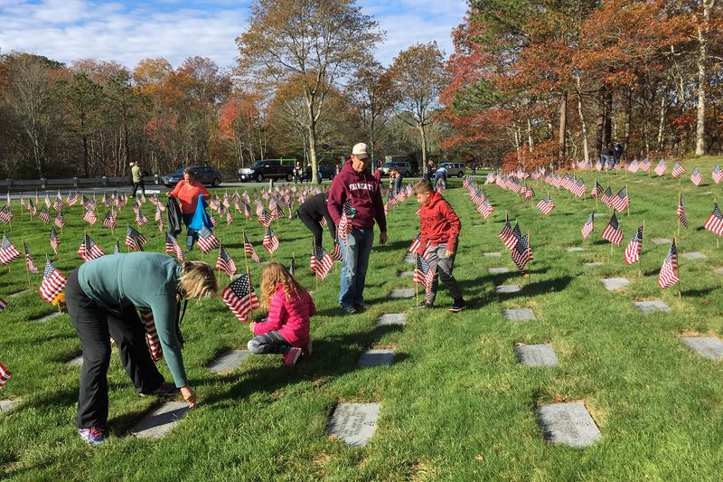 Volunteers place American flags on the graves at the Massachusetts National Cemetery in Bourne, Mass., for Veterans Day. (Alex Ashlock/Here & Now)