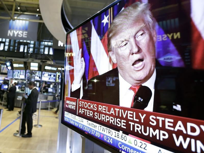 An image of President-elect Donald Trump appears Wednesday on a television screen on the floor of the New York Stock Exchange. Business leaders are taking a wait-and-see approach to his administration.