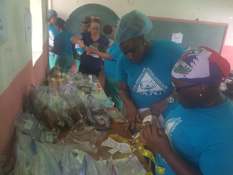 Nurse Chély Paul, center, staffs a makeshift pharmacy with a group from the Haitian American Nurses Association, at a school in Camp Perrin. (Rowan Moore Gerety/WLRN)
