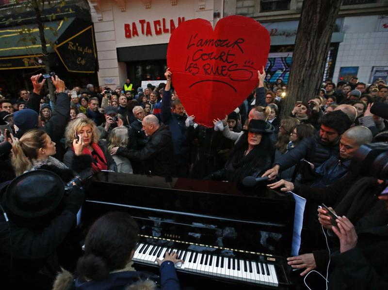 "A woman plays piano, next to a red heart reading ""Love runs through the streets,"" in front of the Bataclan concert hall in Paris on Sunday. The city marked the one-year anniversary of the Nov. 13, 2015, attacks that targeted the concert hall and several other sites, killing 130 people."