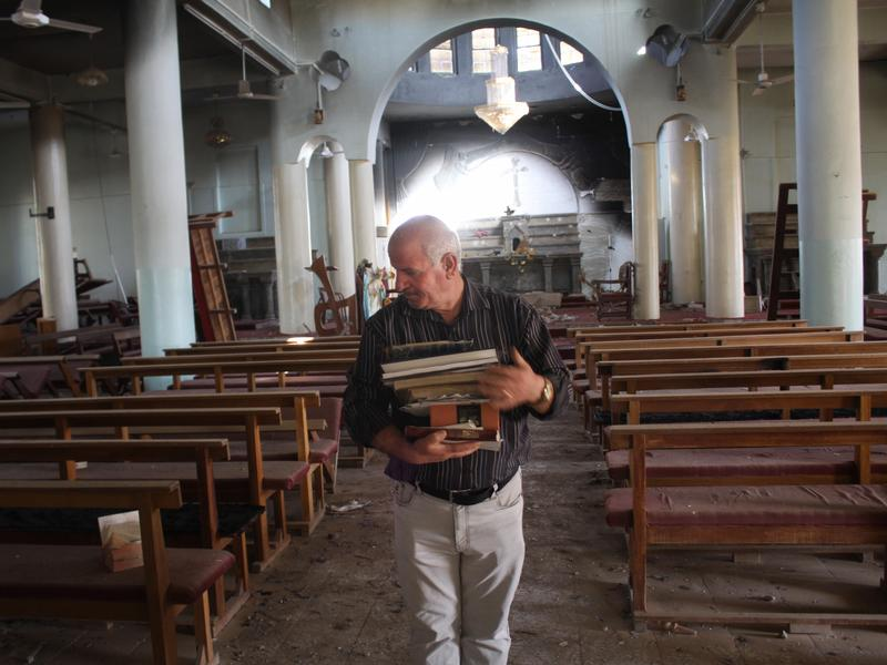 Khalid Yaako Touma, a school teacher and deacon in the village of Karamlesh, collects religious books from one of the churches in the village that ISIS destroyed.
