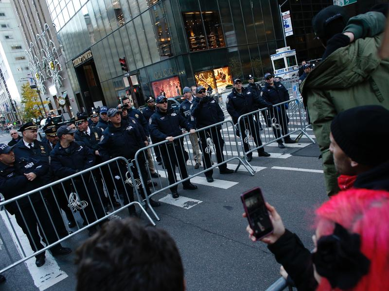New York police officers block the street during a protest against U.S. President-elect Donald Trump in front of Trump Tower on Nov. 12, 2016 in New York. Americans spilled into the streets Saturday for a new day of protests against Trump, even as he appeared to back away from the fiery rhetoric that propelled him to the White House.