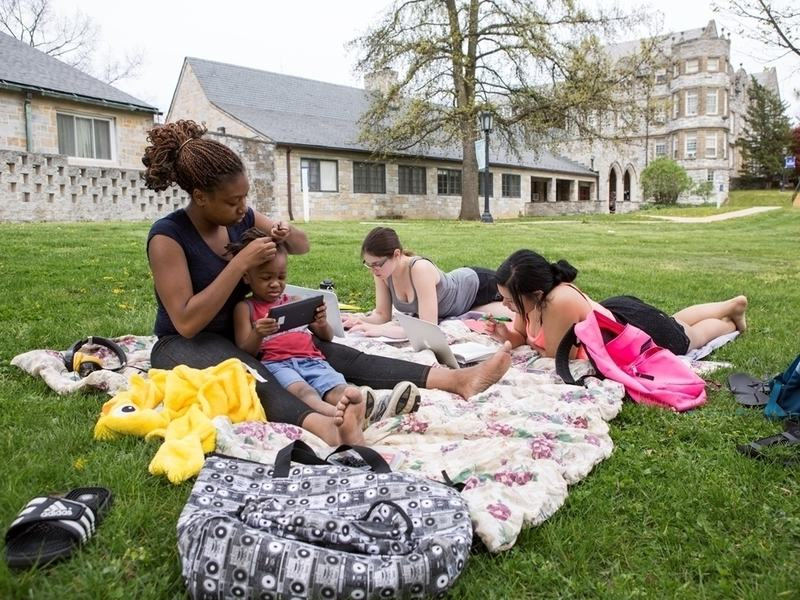 Student Cierra Valentine (left) studies with friends and her son Jeremiah on the lawn at Wilson College in Chambersburg, Pa.