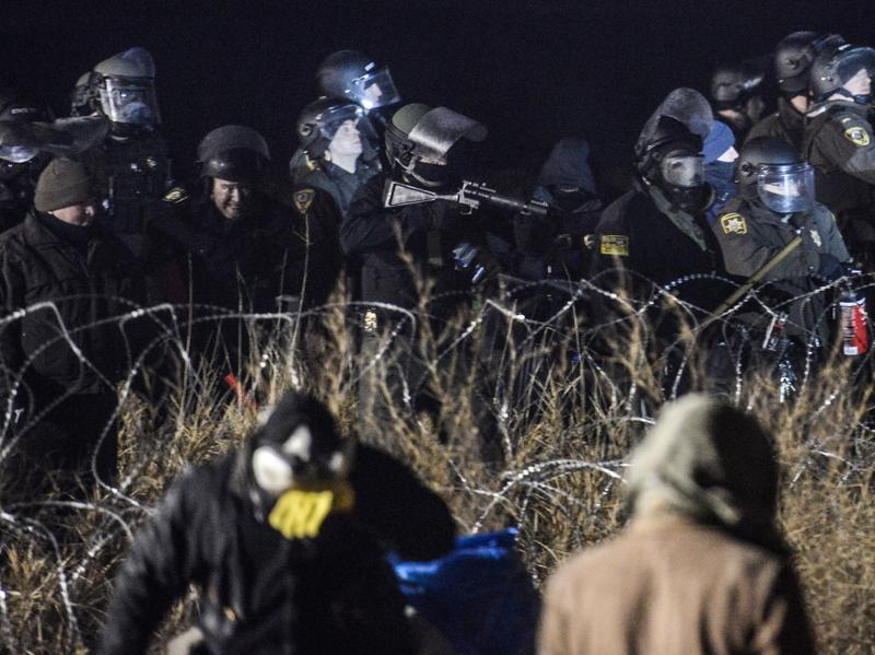Police confront protesters with a rubber bullet gun near Cannon Ball, N.D., on Sunday, during a protest against plans to pass the Dakota Access Pipeline near the Standing Rock Indian Reservation.