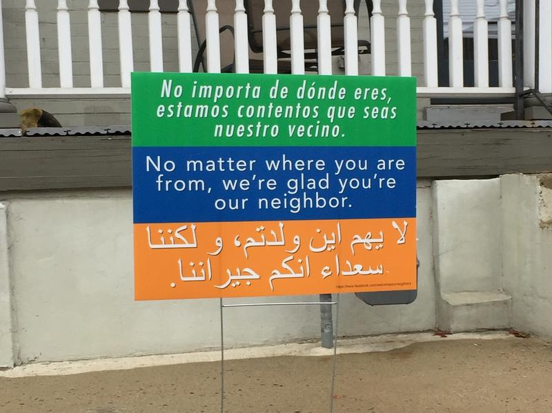 "A sign in Washington, D.C., says ""No matter where you are from, we're glad you're our neighbor,"" in three languages. It's a message that began at a church in Harrisonburg, Va., and is spreading to communities across the country."