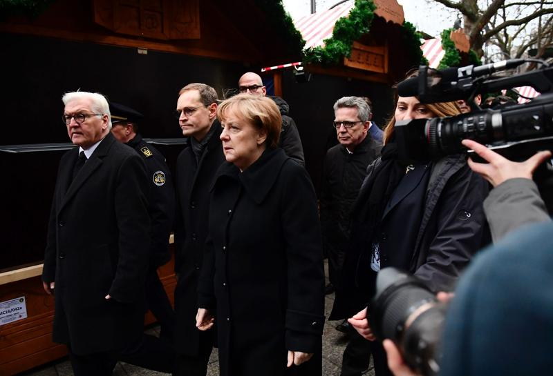 "German Chancellor Angela Merkel (C), German Foreign Minister Frank-Walter Steinmeier (L), German Interior Minister Thomas de Maiziere (4thL) and Berlin's mayor Michael Mueller (2ndL) walk through the Christmas market of the Kaiser-Wilhelm-Gedaechtniskirche (Kaiser Wilhelm Memorial Church), the day after an attack at the nearby Christmas market in central Berlin, on Dec. 20, 2016. German police said they were treating as ""a probable terrorist attack"" the killing of 12 people when the speeding lorry cut a bloody swath through the packed Berlin Christmas market. (Tobias Schwarz/AFP/Getty Images)"