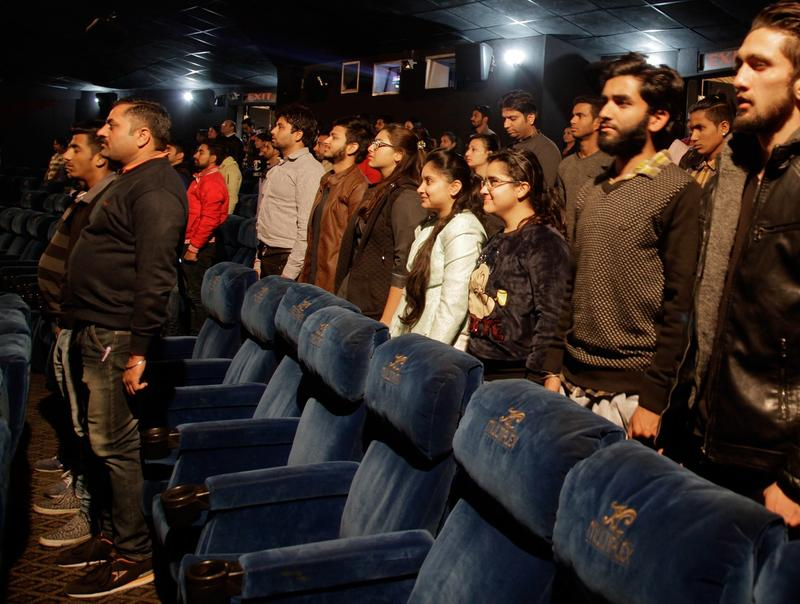 Indian moviegoers stand up as national anthem is played at a movie hall before the screening of a movie in Jammu, India, Tuesday, Dec. 13, 2016.  A ruling by India's Supreme Court in November said that the anthem must be played before every film screening in the country and that audiences must stand. The court said the rule was aimed at instilling a sense of patriotism. (Channi Anand/AP)