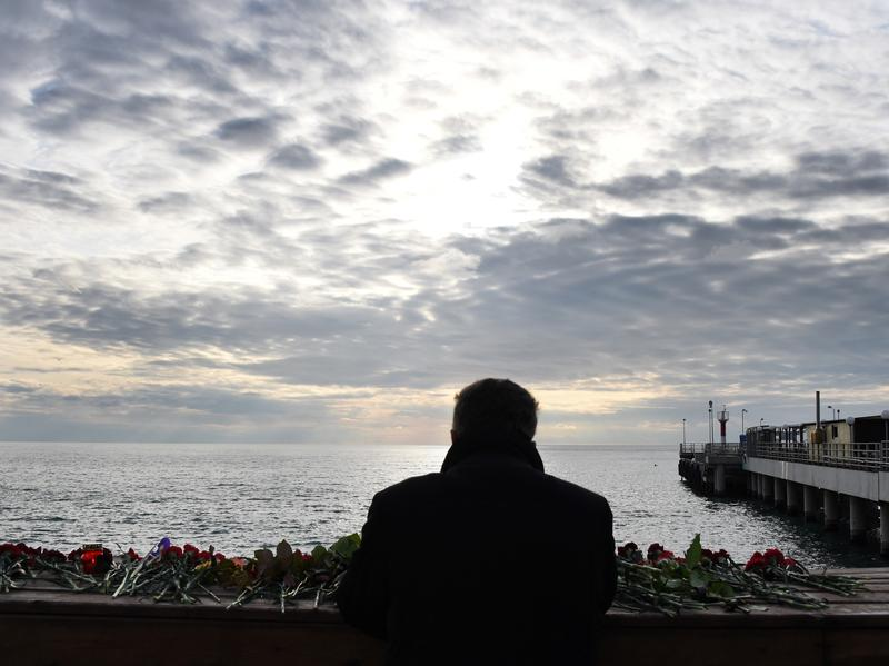 A man looks out at the Black Sea from the coastal city of Sochi, on Monday, a day after a military plane crashed out at sea. The Russian military plane crashed on its way to Syria on Sunday, with no sign of survivors among the 92 on board.