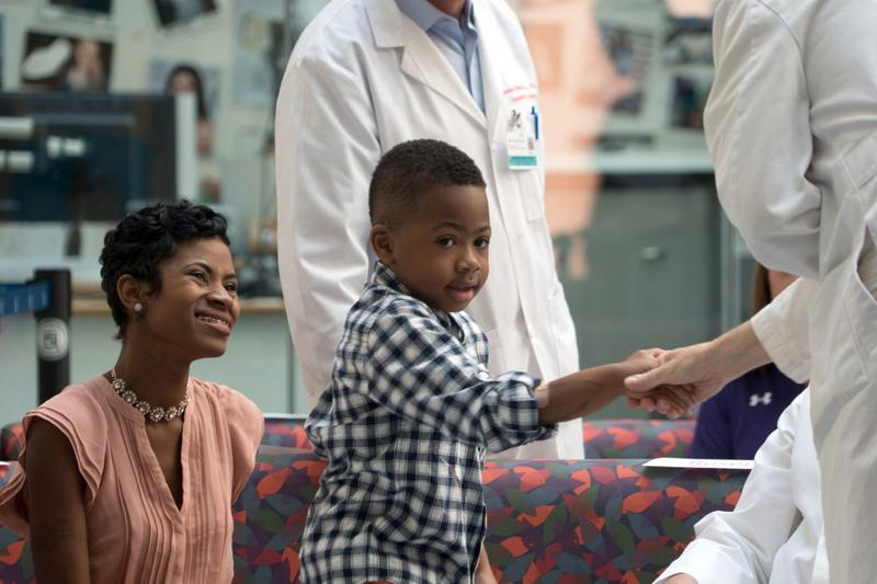 Zion Harvey, center, who received a double hand transplant in July 2015, shakes hands with a health care worker as his mother Pattie Ray, left, smiles during a news conference, Tuesday, Aug. 23, 2016 at The Children's Hospital of Philadelphia in Philadelphia. (Dake Kang/AP)