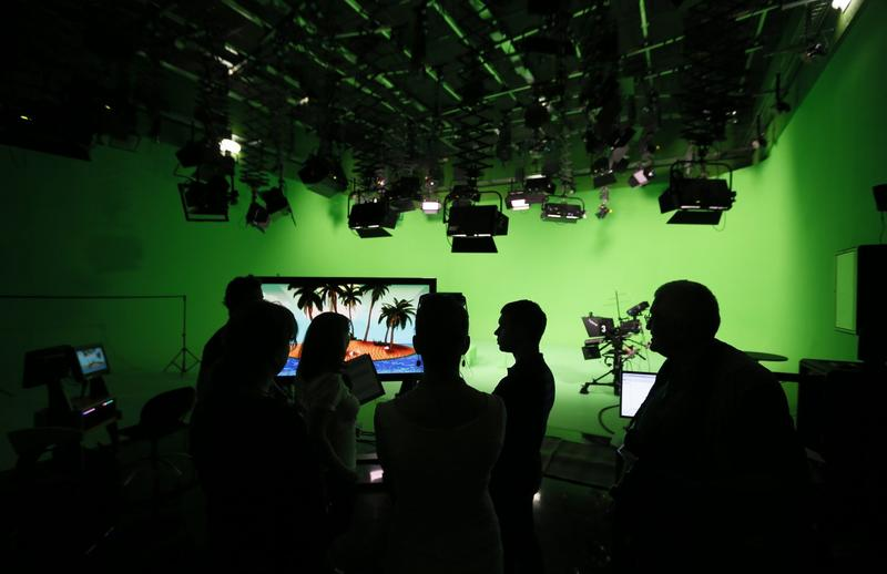 Employees of the state-owned English-language Russia Today (RT) television network are silhouetted against the backdrop at the RT new studio complex in Moscow in June 2013. (Yuri Kochetkov/AFP/Getty Images)