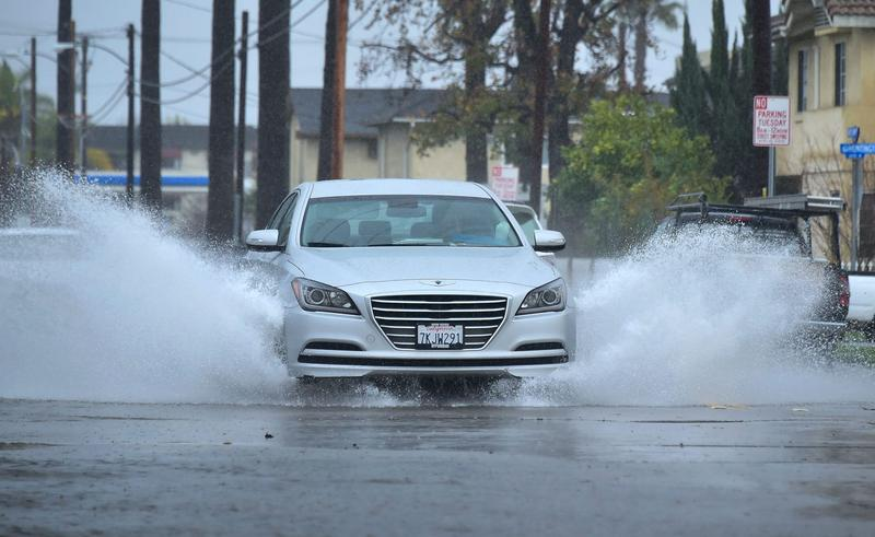 A vehicle is driven along a flooded street in Monterey Park, Calif., on Jan. 23, 2017 following another night of rain. (Frederic J. Brown/AFP/Getty Images)