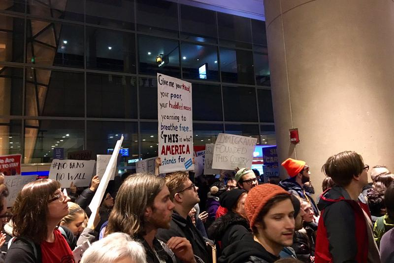 Protesters gathered at Logan Airport's Terminal E Saturday night and early Sunday morning in opposition to President Trump's executive order on immigration. (Shannon Dooling/WBUR)