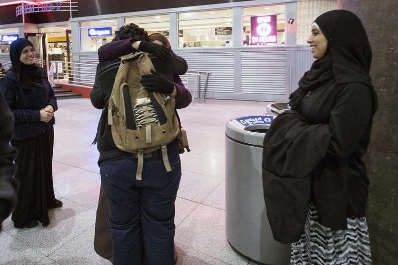 Ali Abdullah Alghazali, 13, from Yemen, center front, hugs his mother as his cousins looks on after he stepped out of an arrival entrance at John F. Kennedy International Airport, in New York. (Alexander F. Yuan/AP)