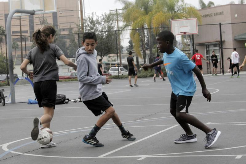 Khalil Aboona (middle) and Sadik Kabera (right) play pick-up soccer. (Erin Siegal McIntyre/KQED)