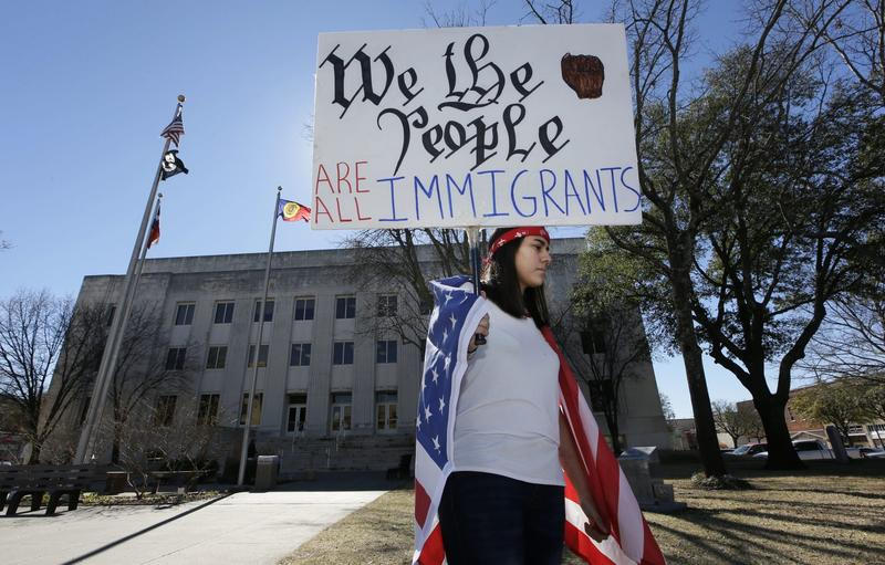 """High school senior Vicky Sosa holds a sign outside the Grayson County courthouse in downtown Sherman, Texas, Thursday, Feb. 16, 2017. In an action called """"A Day Without Immigrants,"""" immigrants across the country are expected to stay home from school, work and close businesses to show how critical they are to the U.S. economy and way of life. (LM Otero/AP)"""