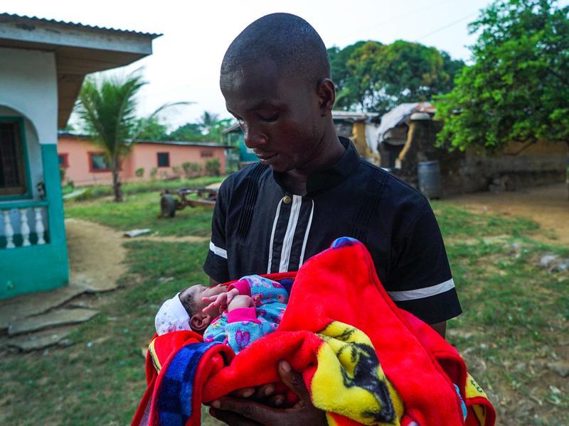 James Harris holds his newborn son, Jeremiah Solomon Karwah.