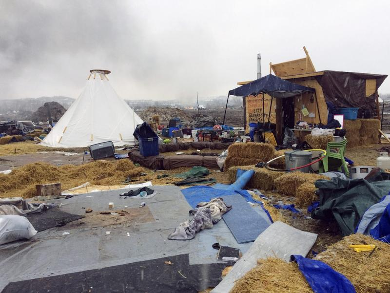 Refuse remains in the Dakota Access pipeline opponents' main protest camp as a fire burns in the background in southern North Dakota near Cannon Ball, N.D., on Wednesday, Feb. 22, 2017, as authorities prepare to shut down the camp in advance of spring flooding season. (Blake Nicholson/AP)