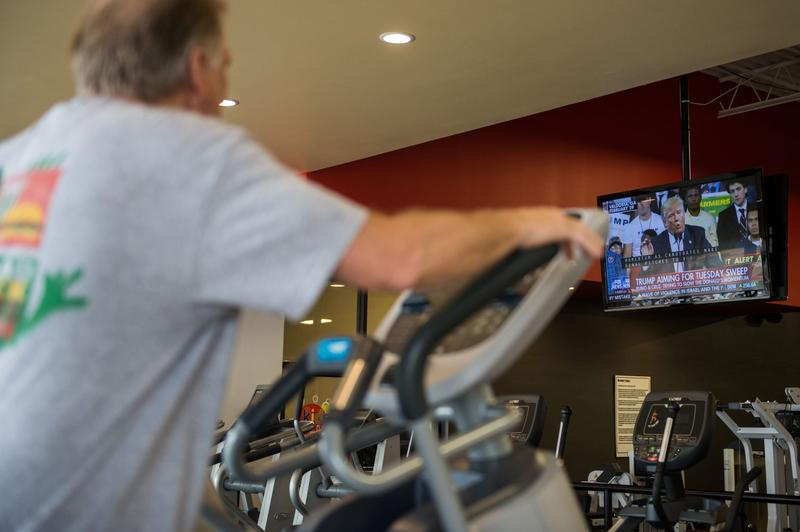 A man watches election coverage broadcast as he works out at a fitness training facility in March 2016 in Conway, Ark. (Michael B. Thomas/AFP/Getty Images)