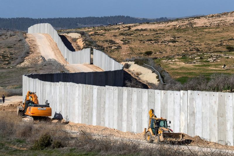 A picture taken near the southern kibbutz of Lahav on Feb. 7, 2017, shows workers building a new section of the controversial Israeli separation wall dividing Israel from the West Bank. (Jack Guez/AFP/Getty Images)
