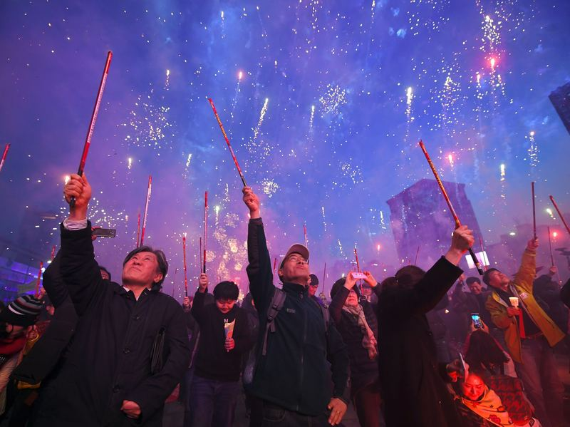 South Korean demonstrators shoot off firecrackers in Seoul on March 11, 2017 to celebrate the impeachment of Park Geun-Hye during a candlelit rally demanding the arrest of the ousted president.