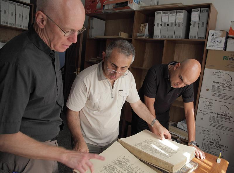 Father Columba Stewart (left), Father Nageeb Michael (center) and Walid Mourad examine a printed Bible at the Dominican Priory in Qaraqosh, Iraq.  (AP Photo/Courtesy Hill Museum & Manuscript Library)