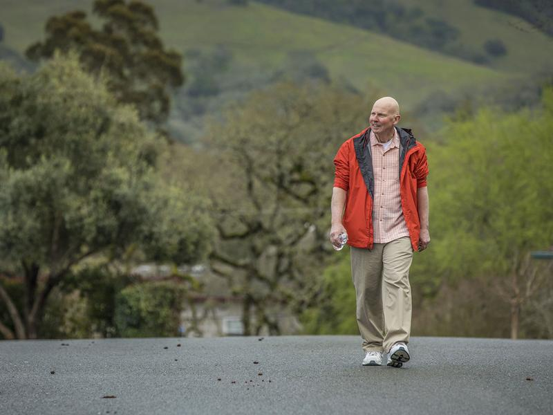 Cancer patient John Krahne has delayed taking a prescribed cancer drug because it was too expensive. He walks near his home in Santa Rosa, Calif.