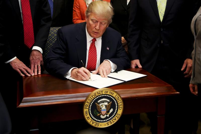 President Donald Trump signs an executive order to begin the rollback of environmental regulations put in place by the Obama administration on Feb. 28, 2017 (Aude Guerrucci - Pool/Getty Images)