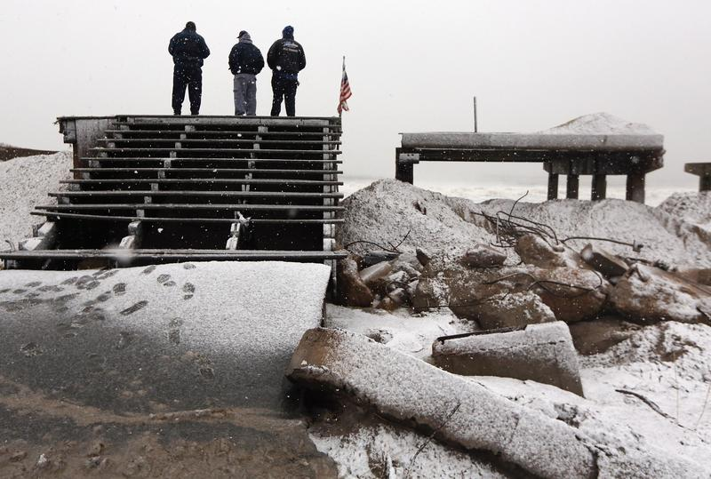 People stand on a destroyed section of boardwalk to check the storm's approach as a nor'easter arrives in New York City on November 7, 2012.