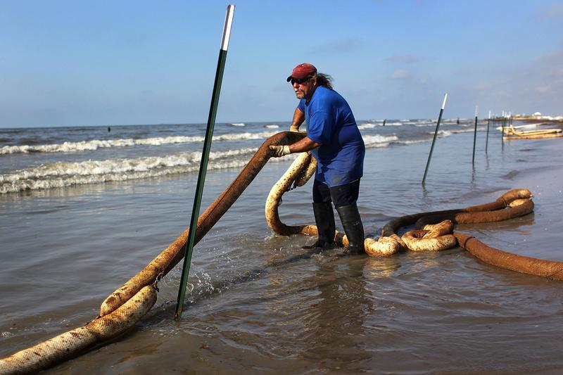 BP cleanup worker Perry LeBoef stretches an oil-soaked boom along a beach on May 23, 2010 on Elmer's Island, Louisiana. Officials now say that it may be impossible to clean the oil-affected wetlands.