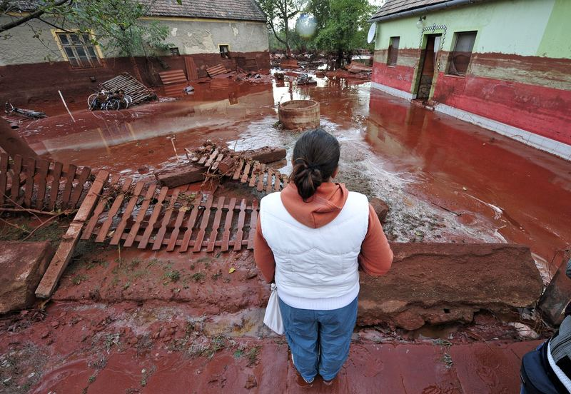 A woman contemplates the damage in Devecser, about 150 kms southwest of Budapest, on October 5, 2010 after the village was flooded on October 4 by toxic red sludge from a local aluminium plant.