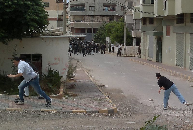 Men throw stones at riot police during clashes in the Mediterranean coastal town of Banias, on May 27, 2011, as Syria braced for more anti-government protests, called for by pro-reform activists.