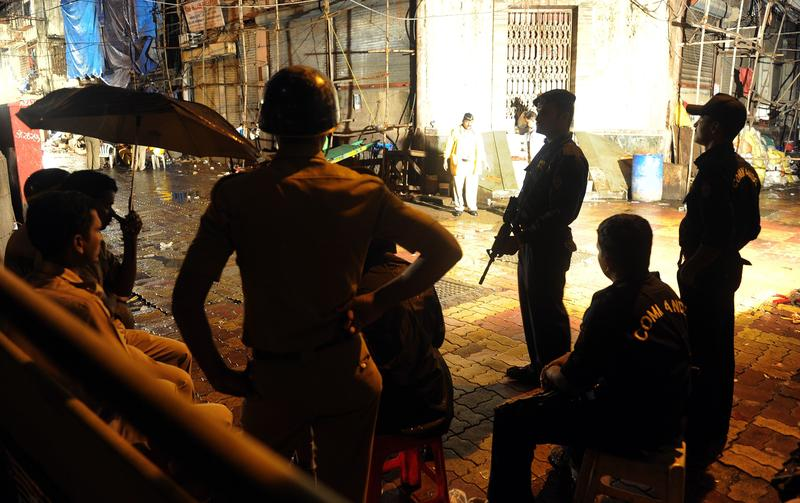 Mumbai police and commandos stand guard near the site of bomb blast at Zaveri Bazar in Mumbai on July 13, 2011.