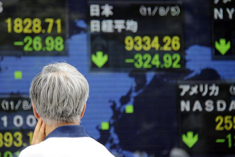 A businessman looks at an electric quotation board flashing the stock prices at a window of a security company in central Tokyo on August 5, 2011. Tokyo shares plunged 395.09 points or 4.09 percent.