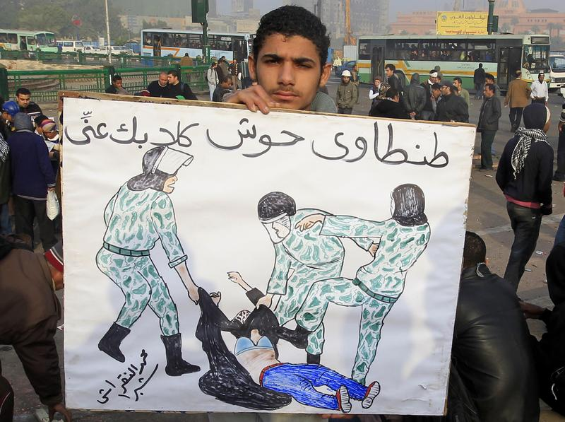 An Egyptian protester's sign reads: '(Field Marshal) Tantawi, get your dogs off me' and depicts a veiled woman who was beaten by military police, during a demonstration at Tahrir Square on Dec. 19.