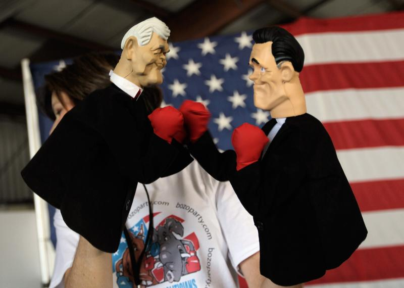 Lynn Coffin holds boxing hand puppets of Newt Gingrich and Mitt Romney in Sarasota, Florida.