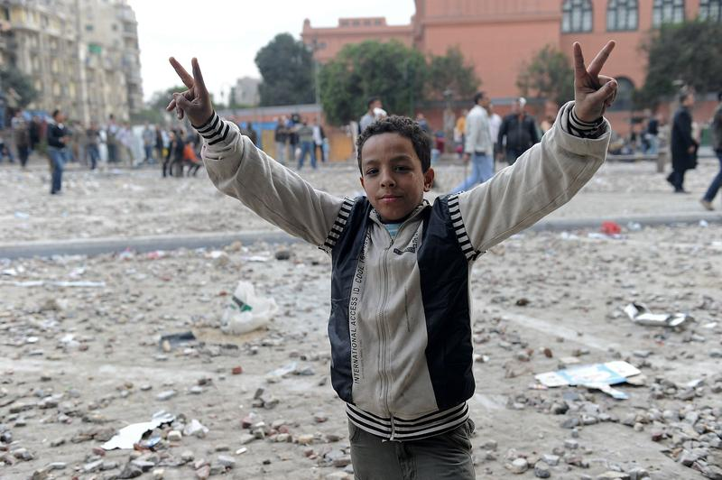 A young Egyptian anti-government demonstrator flashes victory signs as a stone battle rages between fellow demonstrators and pro-regime opponents at Cairo's Tahrir Square on February 3, 2011