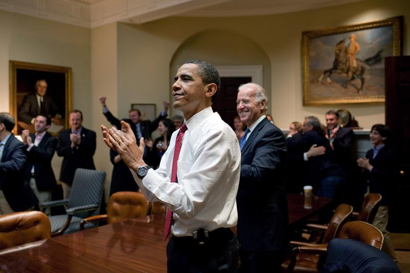 U.S. President Barack Obama, Vice President Joe Biden, and senior staff applaud in the Roosevelt Room of the White House, as the House of Representatives passes the health care reform bill.