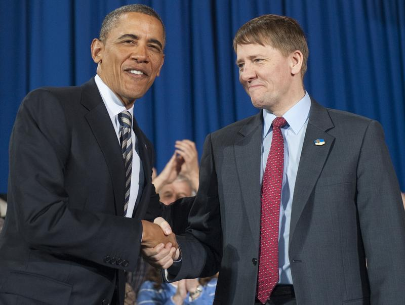 US President Barack Obama shakes hands with Richard Cordray (R) prior to speaking about the economy.