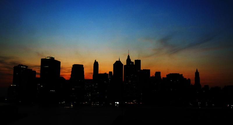 The sun sets over the Manhattan skyline August 14, 2003 during a major power outage affecting a large part of the north eastern United States and Canada.