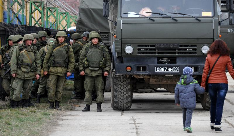 Military personnel stand near a Russian-made Kamaz truck in the eastern Crimea'a port city of Feodosiya on March 2, 2014.