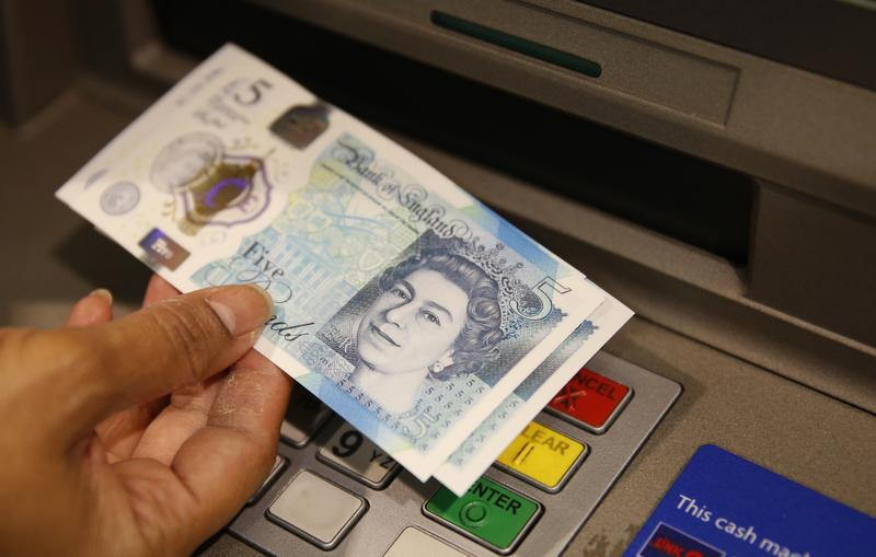 Sept. 13, 2016: A member of staff at a branch of Halifax bank, in London, displays a new British 5 pound sterling note, made from polymer, which is being launched Tuesday.