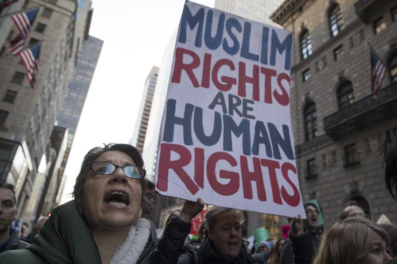 Image result for Muslims hold a sign as demonstrators against Donald Trump in New York