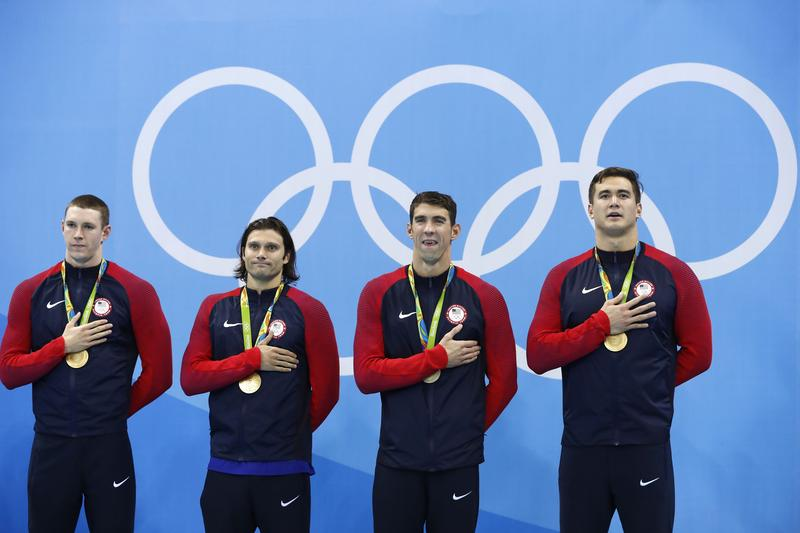 The U.S. goid medal 4x100-meter medley team listens to the controversial arrangement of the national anthem at the Olympic Aquatics Stadium in Rio.