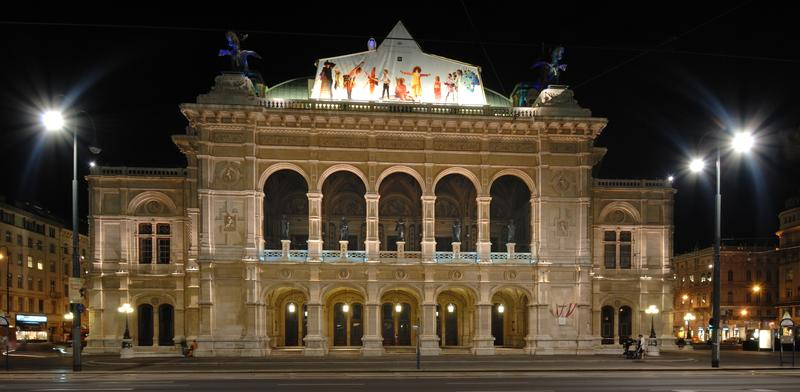 The Vienna State Opera house is illuminated at night.