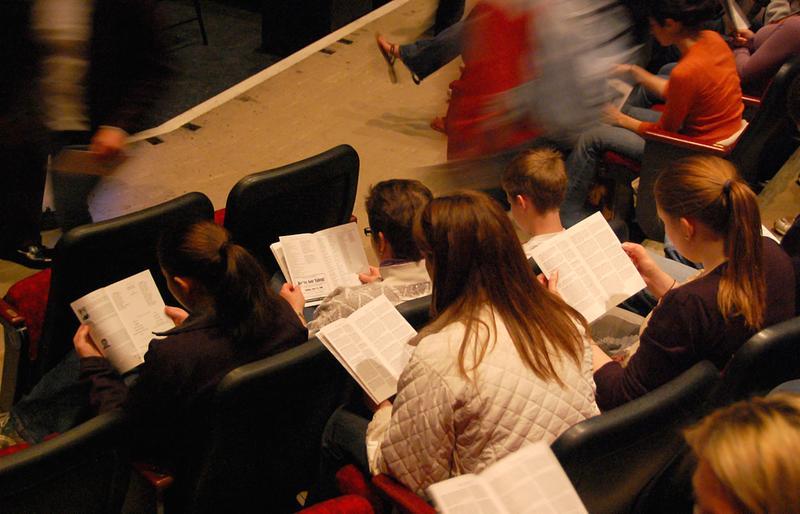 Theater-goers reading program books