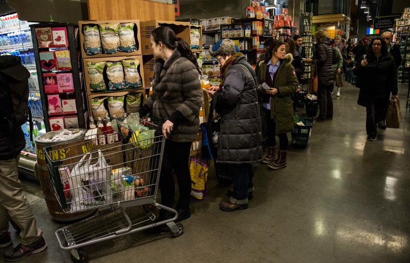 Shoppers at Whole Foods wait on line as the snowstorm begins