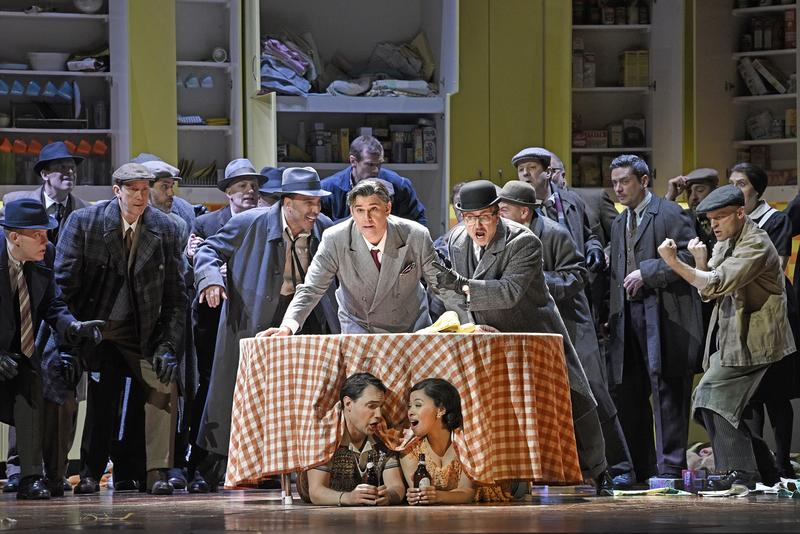Francesco Demuro as Fenton and Golda Schultz as Nannetta (under table) and (left to right, behind table) Richard Bernstein as Pistola, Juan Jesús Rodríguez as Ford, and Tony Stevenson as Dr. Caius.