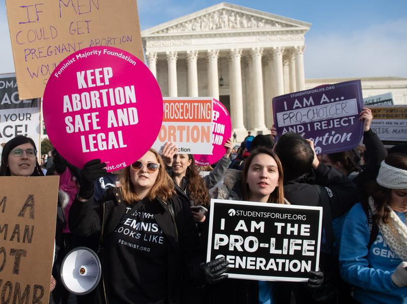 Pro-abortion rights activists hold signs alongside anti-abortion-rights activists outside the Supreme Court last month.