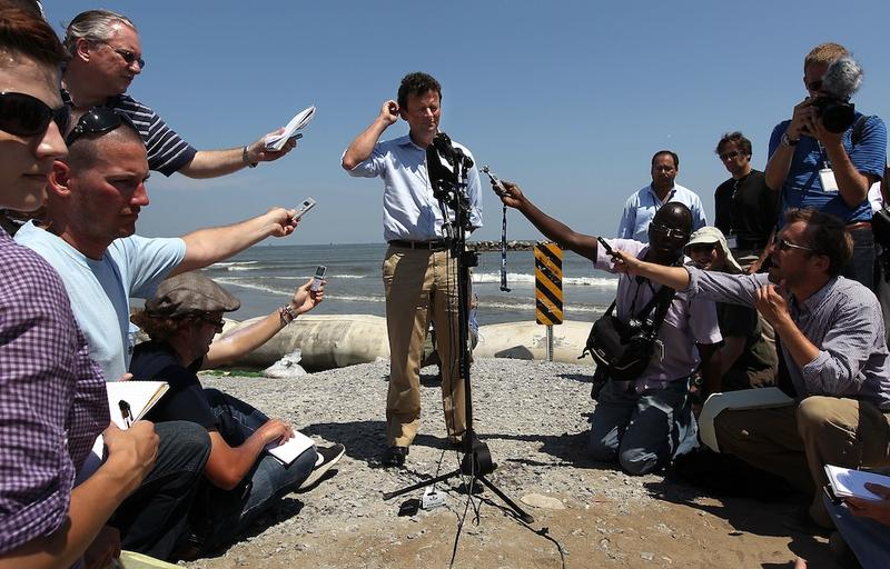 BP CEO Tony Hayward (C) answers questions from the media on an oil-stained beach on May 24, 2010 at Port Fourchon, Louisiana. Hayward said that BP is doing everything possible to clean up the spill.